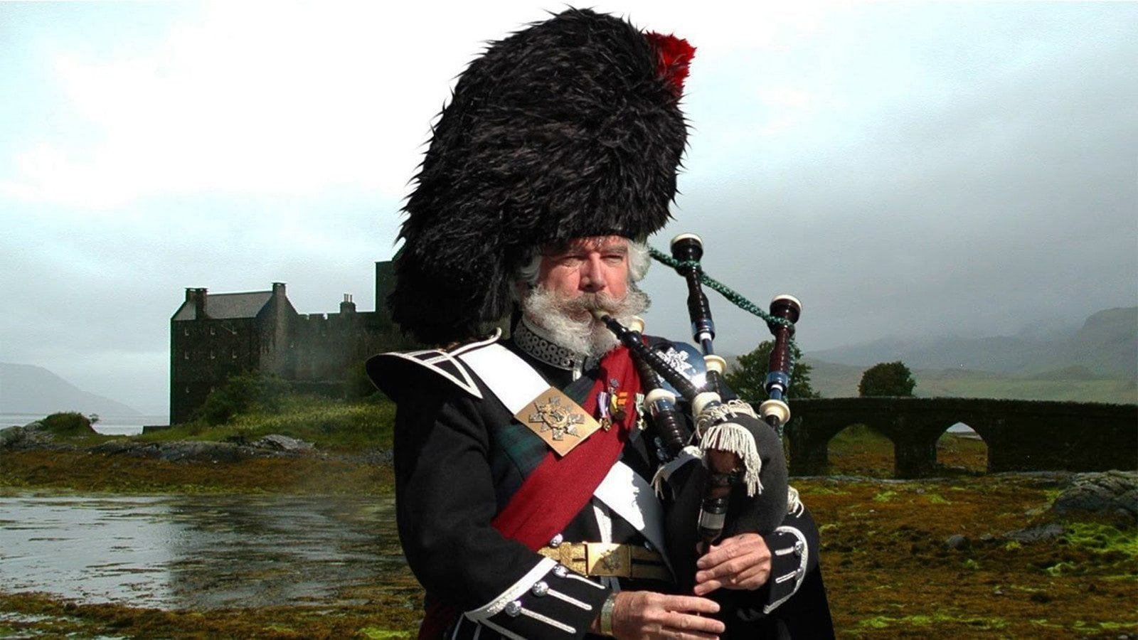 Photo of a Scotts Guardsman bagpiper and a castle and the mountains behind him.