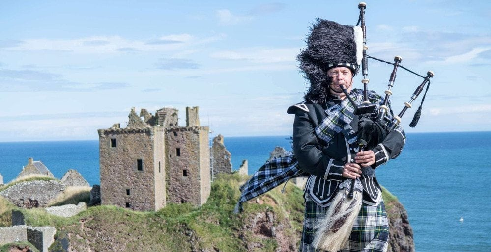 Photo of a Scotts Guardsman bagpiper and a castle and the sea behind him.