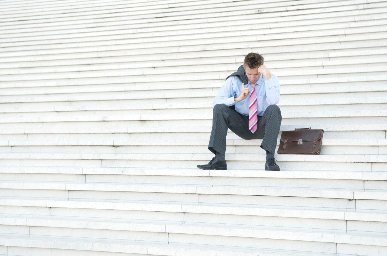March Jobs Report Nothing Moving: photo of unemployed man sitting on stone steps.